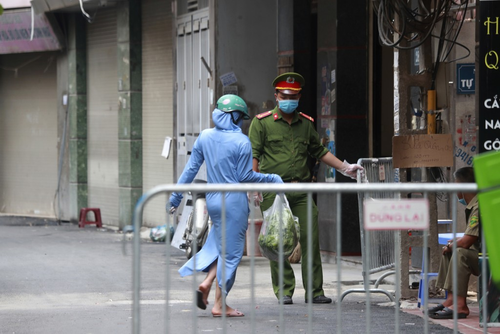 A woman leaves the food shopping for her relatives at the barricaded entrance to the residence of a confirmed COVID-19 case in Hanoi, Vietnam on Wedne...