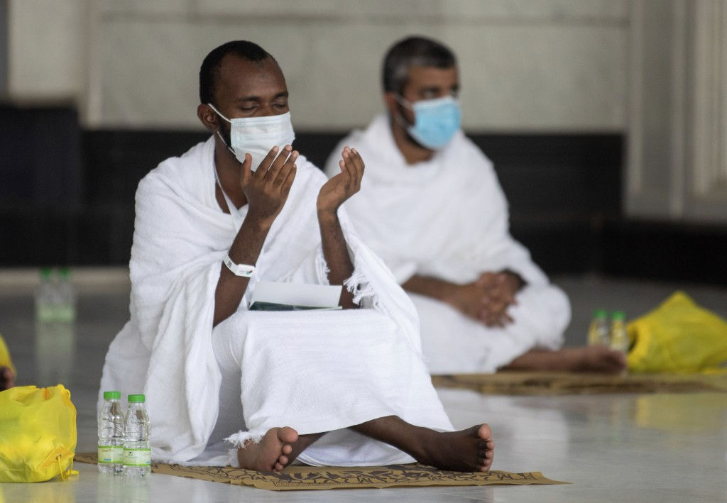 In this photo released by the Saudi Media Ministry, a limited numbers of pilgrims pray in the first rituals of the hajj, as they keep social distancin...