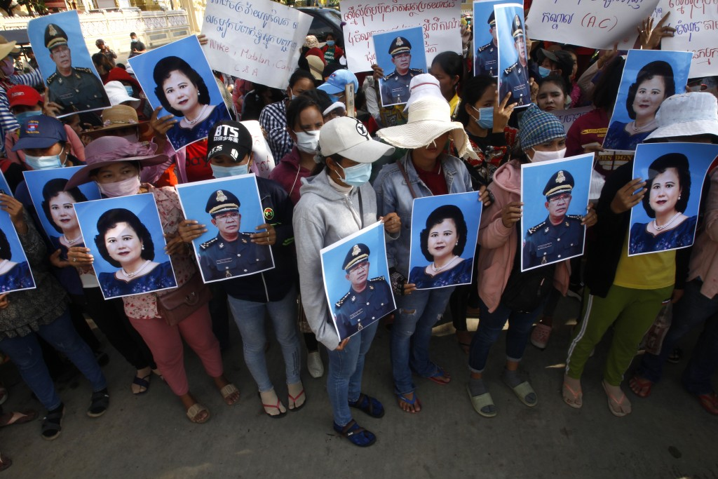 Cambodian garment workers holding the portraits of Prime Minister Hun Sen and his wife Bun Rany stage a protest rally near the prime minister's reside...
