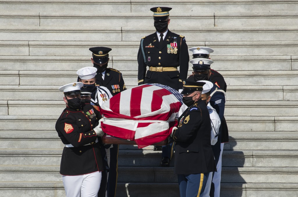 The flag-draped casket of the late Rep. John Lewis, D-Ga., is carried by a joint services military honor guard down the East Front steps of the Capito...