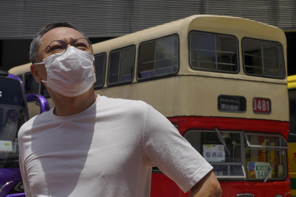 "Occupy Central leader Benny Tai stands in front of a vintage double-deck bus used as a polling center for an unofficial ""primary"" for pro-democracy ca..."