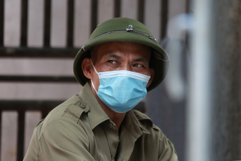 A militia officer guards the barricaded entrance of an alley where one of its residents has COVID-19 in Hanoi, Vietnam on Wednesday, July 29, 2020. Vi...