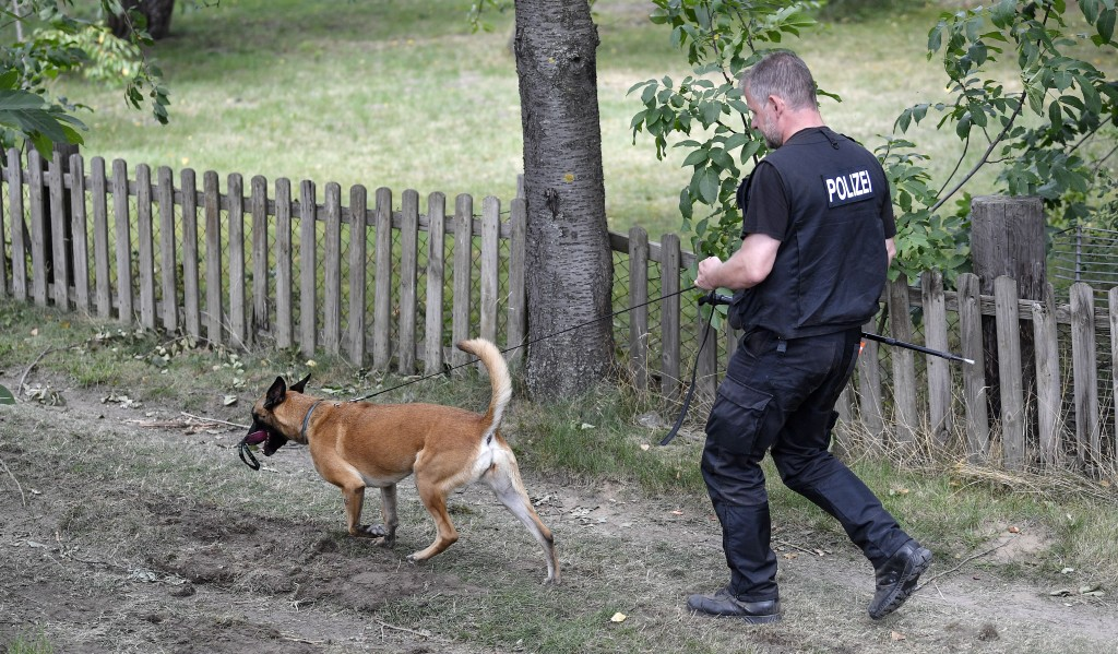 Germany police officers search with dogs an allotment garden plot in Seelze, near Hannover, Germany, Wednesday, July 29, 2020. Police have begun searc...
