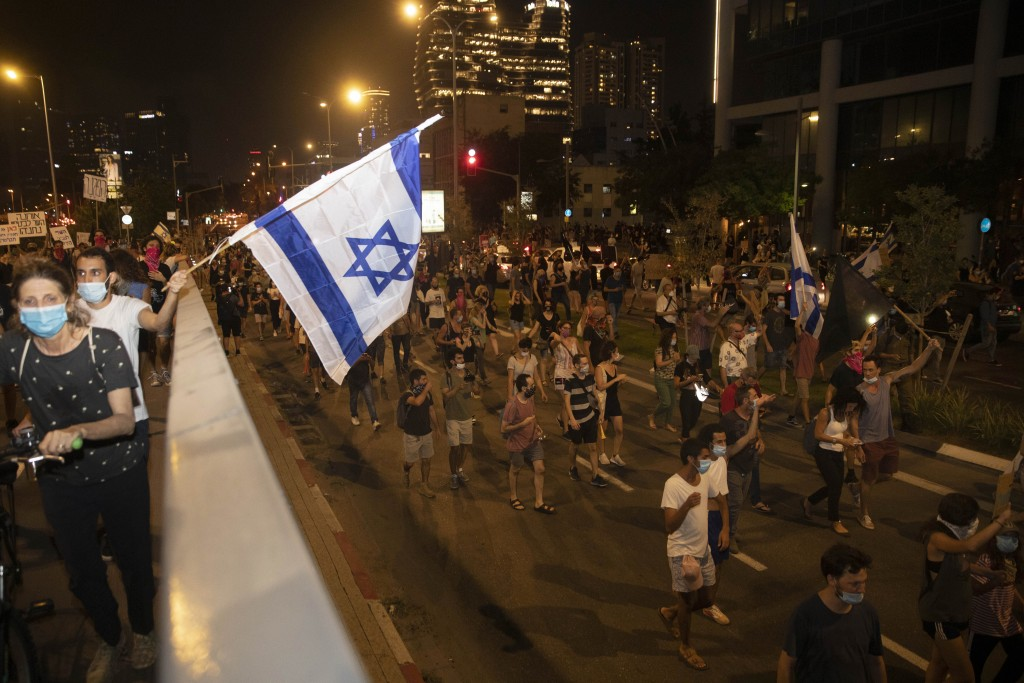 Israelis march on the street during a protest against corruption near the house of Israel's Minister of Public Security in Tel Aviv, Israel, Tuesday, ...