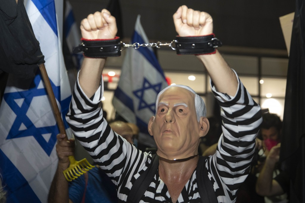 An Israeli protester wearing a mask depicting Israeli Prime Minister Benjamin Netanyahu chant slogans during a protest against corruption near the hou...