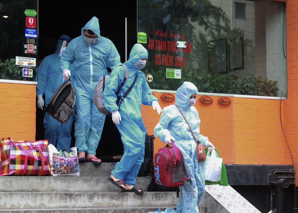 People walk toward an ambulance to be driven to a hospital for quarantine relating to a suspected COVID-19 case in Hanoi, Vietnam, Wednesday, July 29,...