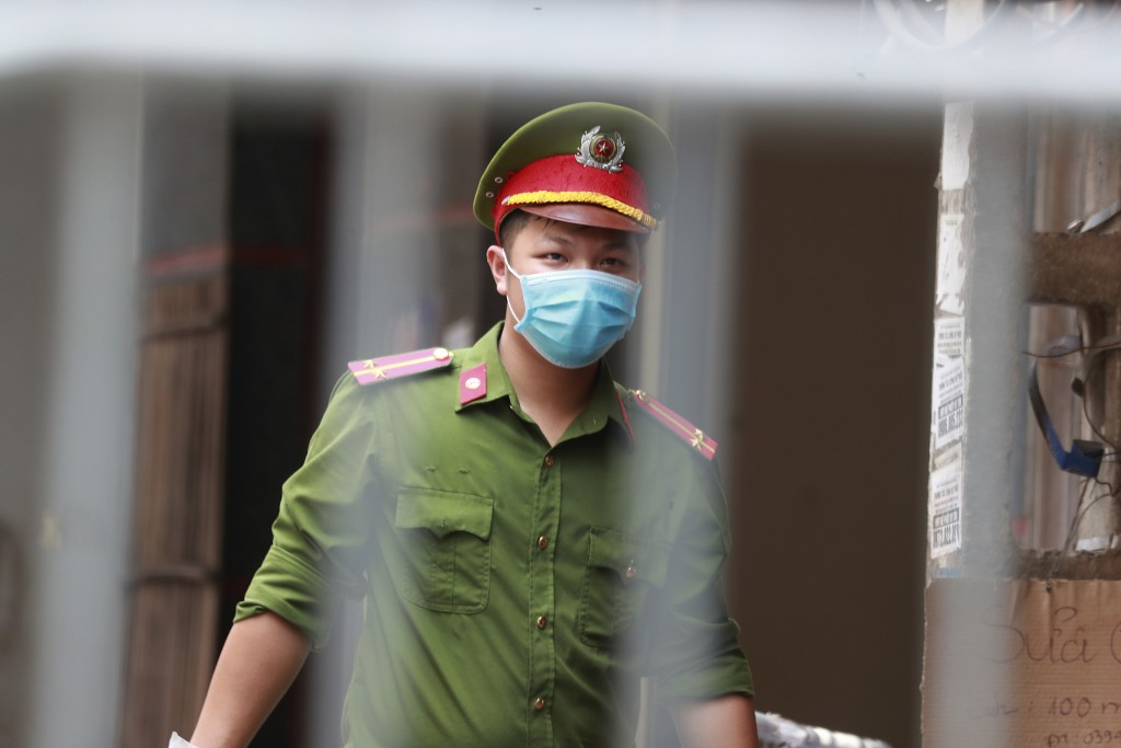 A police officer guards the barricaded entrance of an alley where one of its residents is has COVID-19 in Hanoi, Vietnam on Wednesday, July 29, 2020. ...