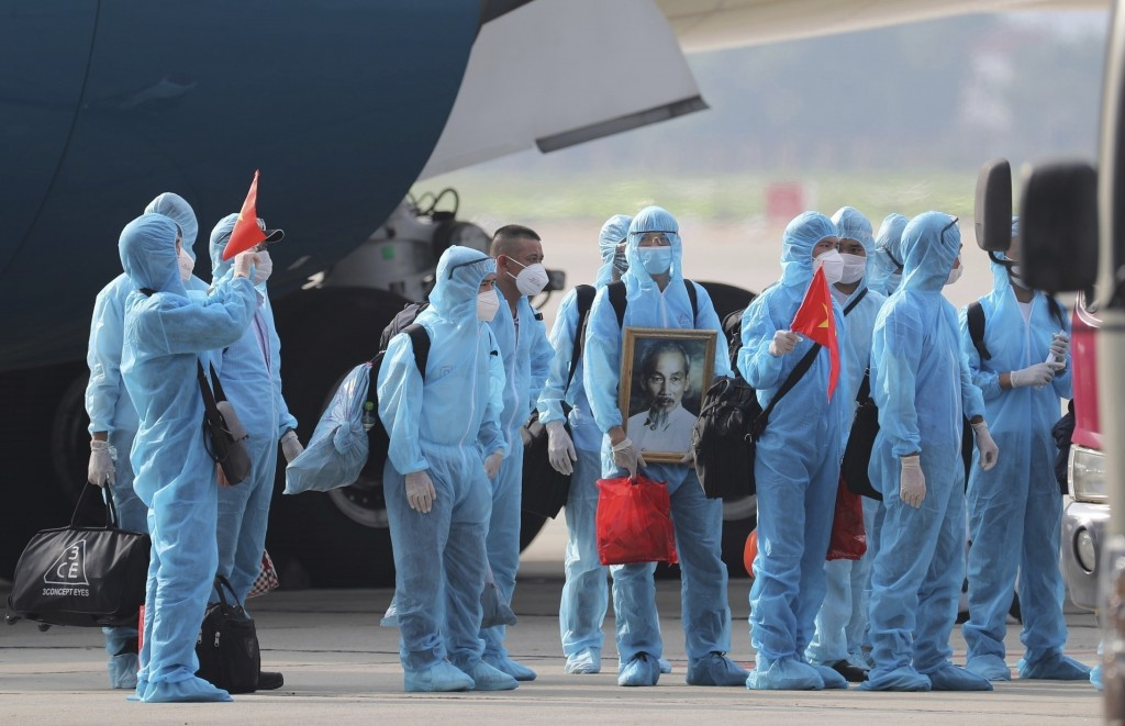 Vietnamese COVID-19 patients in protective gear, holding Vietnamese flags and carrying a portrait of the national leader Ho Chi Minh, arrive at the No...