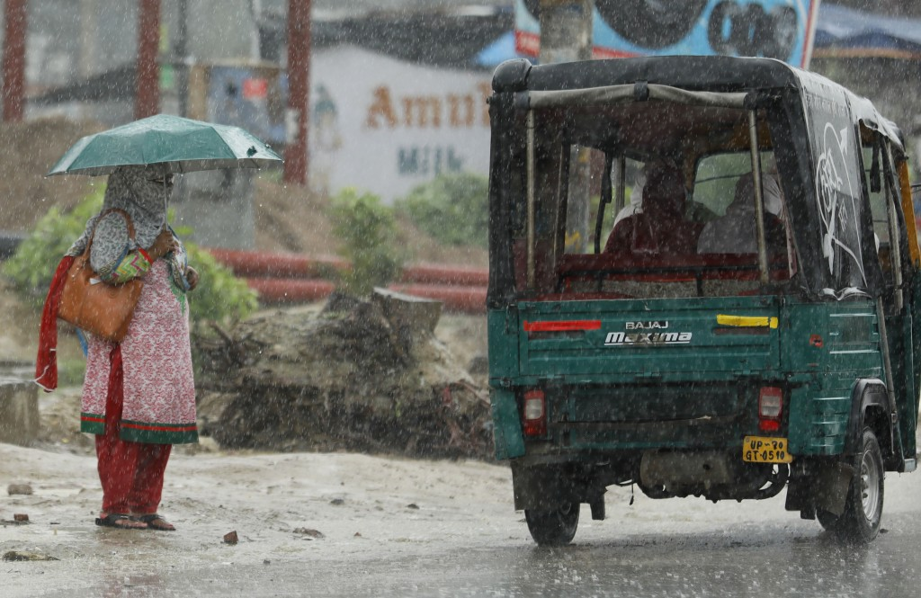 A woman with her face covered stands in the rain in Prayagraj, India, Wednesday, July 29, 2020. India is the third hardest-hit country by the pandemic...
