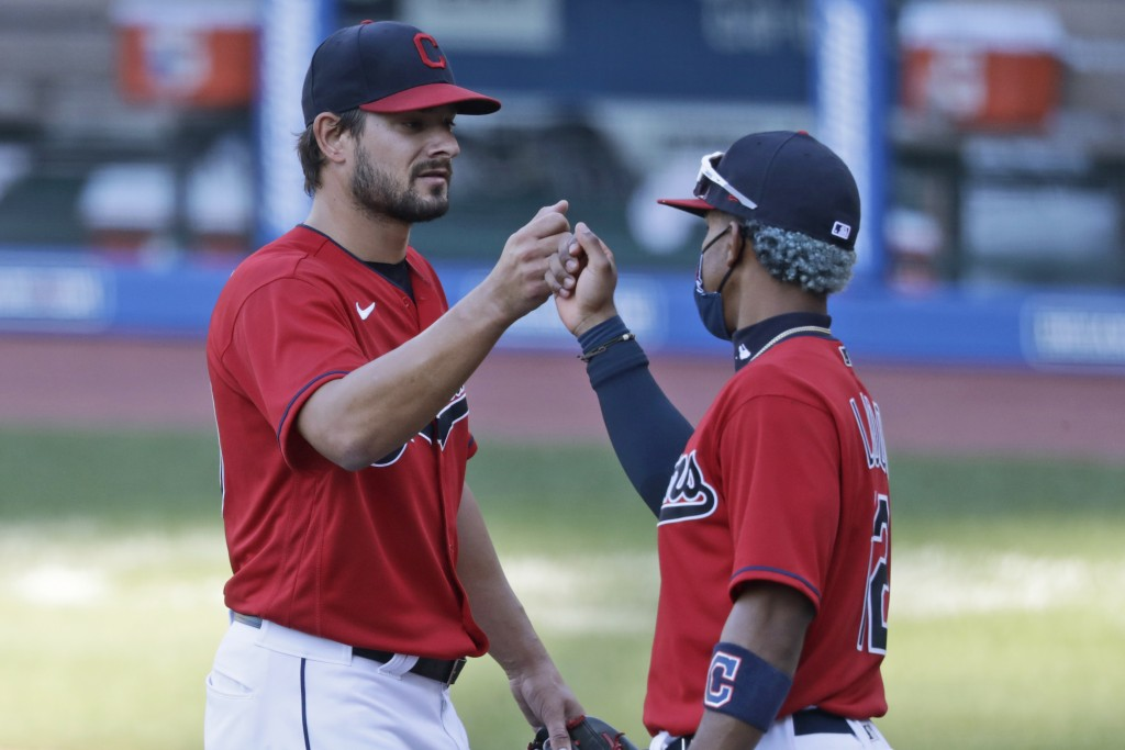 Cleveland Indians relief pitcher Brad Hand, left, is congratulated by Francisco Lindor after the Indians defeated the Chicago White Sox 4-3 in the fir...