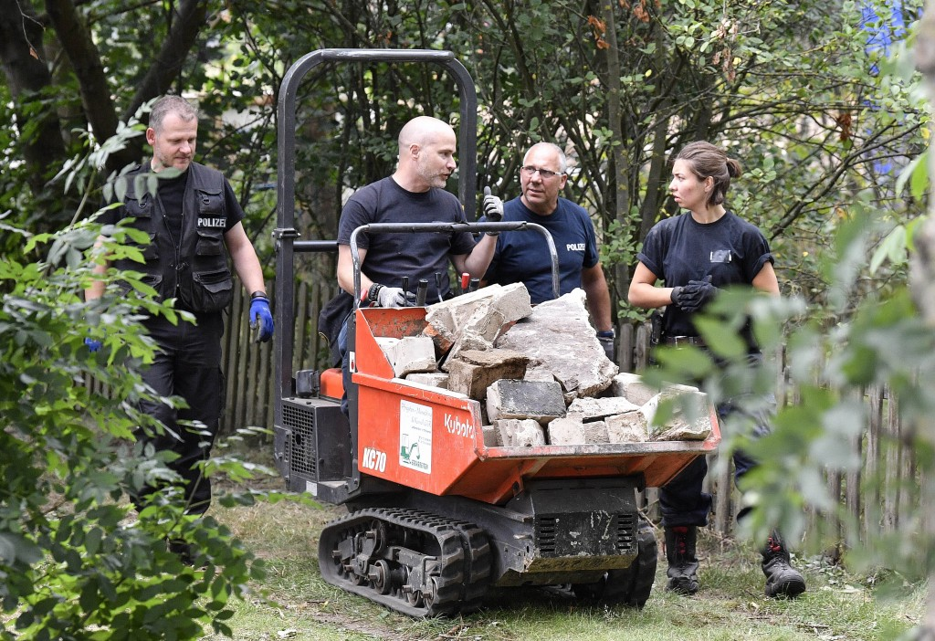 Germany police officers search an allotment garden plot in Seelze, near Hannover, Germany, Tuesday July 28, 2020. Police have begun searching an allot...