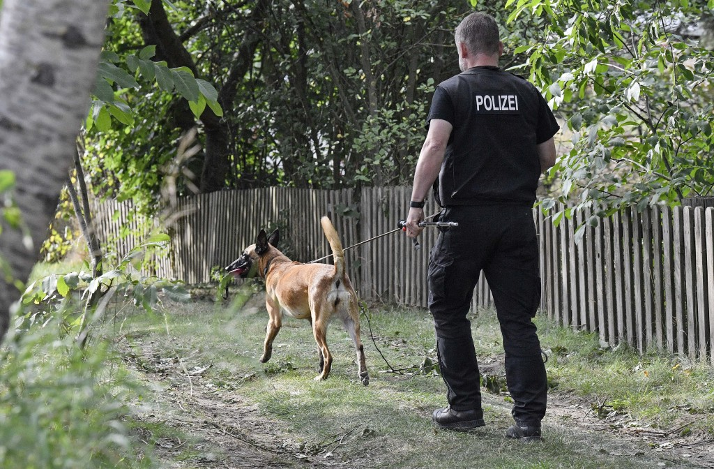 A German police officer walks with a search dog during an investigating at an allotment garden plot in Seelze, near Hannover, Germany, Tuesday July 28...