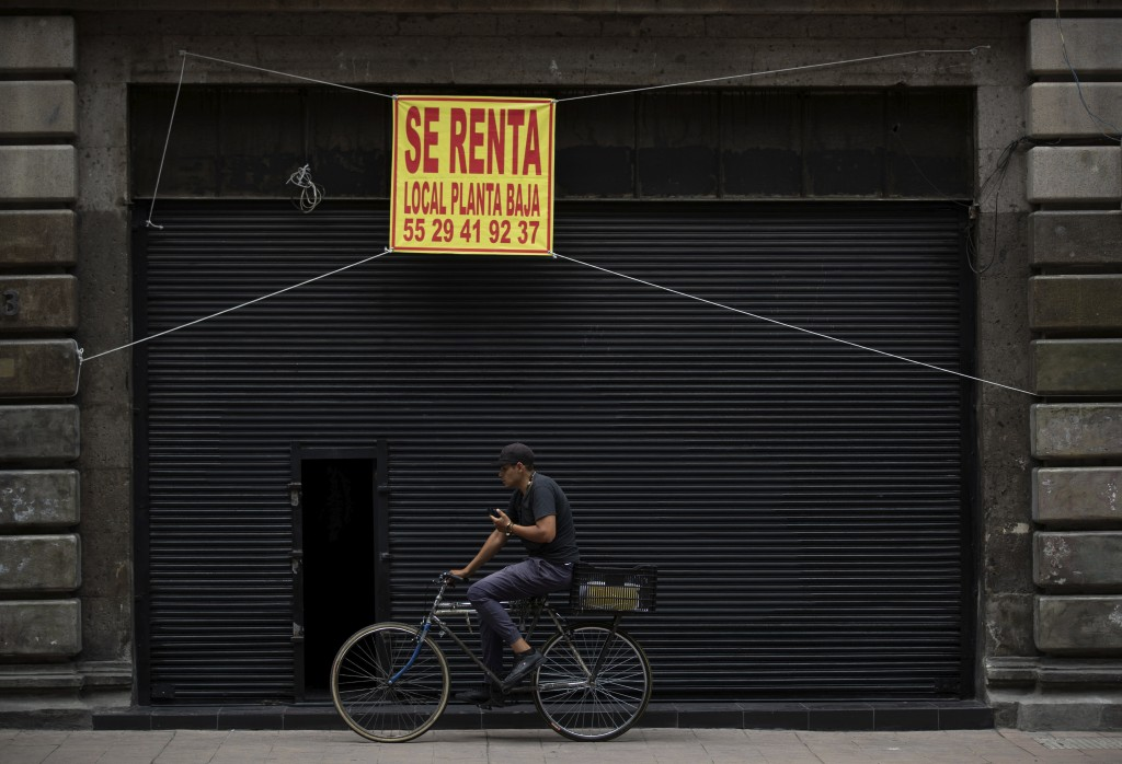 A man rides his bike past a shuttered local that is being offered for rent in downtown Mexico City, Tuesday, July 28, 2020. With the country facing a ...