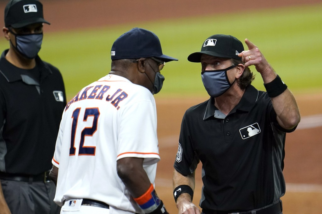 Umpire Chris Guccione, right, talks to Houston Astros manager Dusty Baker (12) after both benches emptied onto the field after the sixth inning of a b...