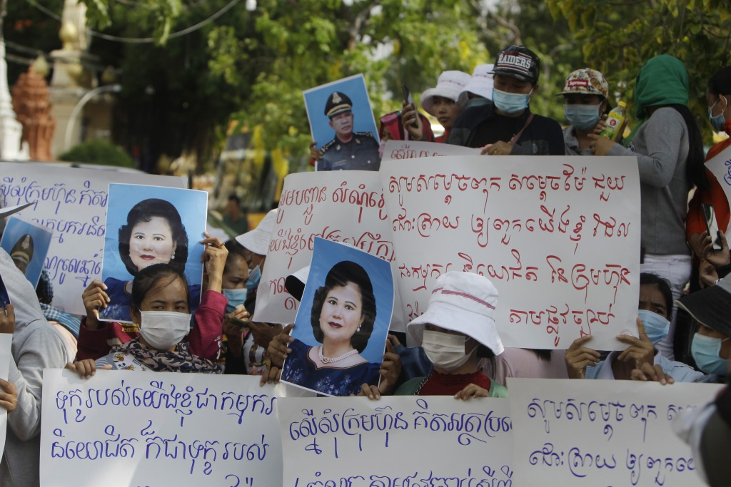 Cambodian garment workers hold slogans and portraits of Prime Minister Hun Sen and his wife Bun Rany during a protest near the prime minister's reside...