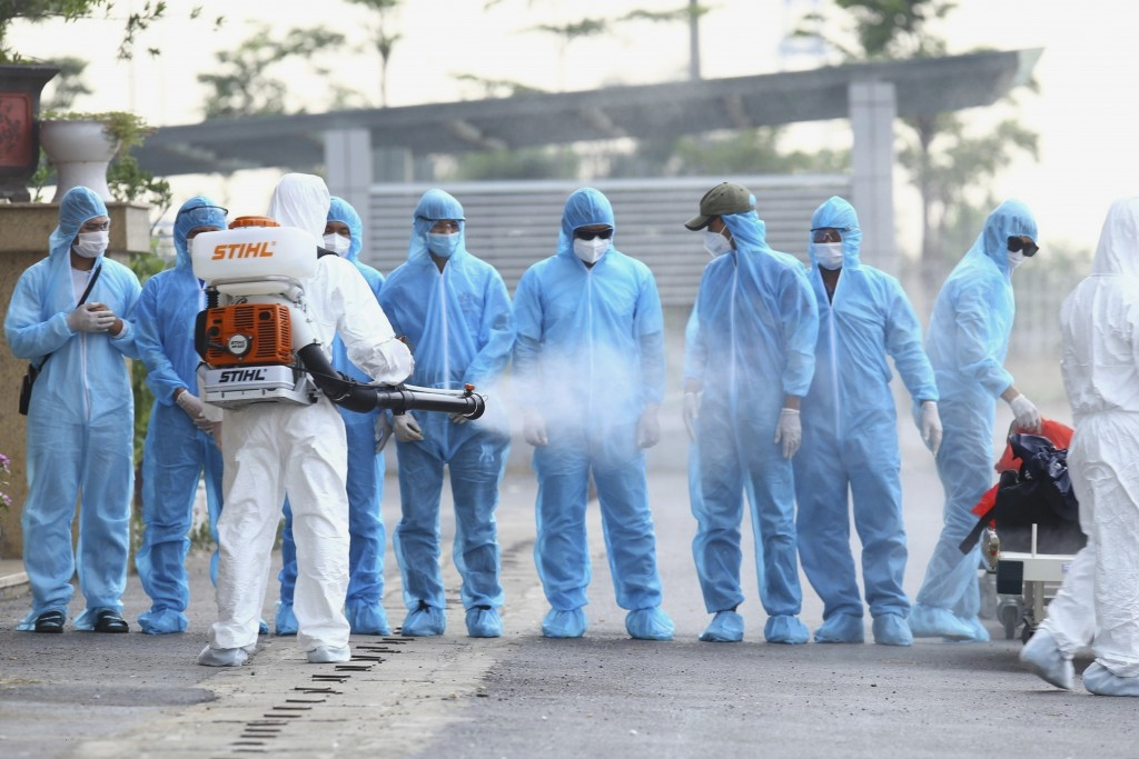 A health worker disinfects arriving Vietnamese COVID-19 patients at the national hospital of tropical diseases in Hanoi, Vietnam on Wednesday, July 29...