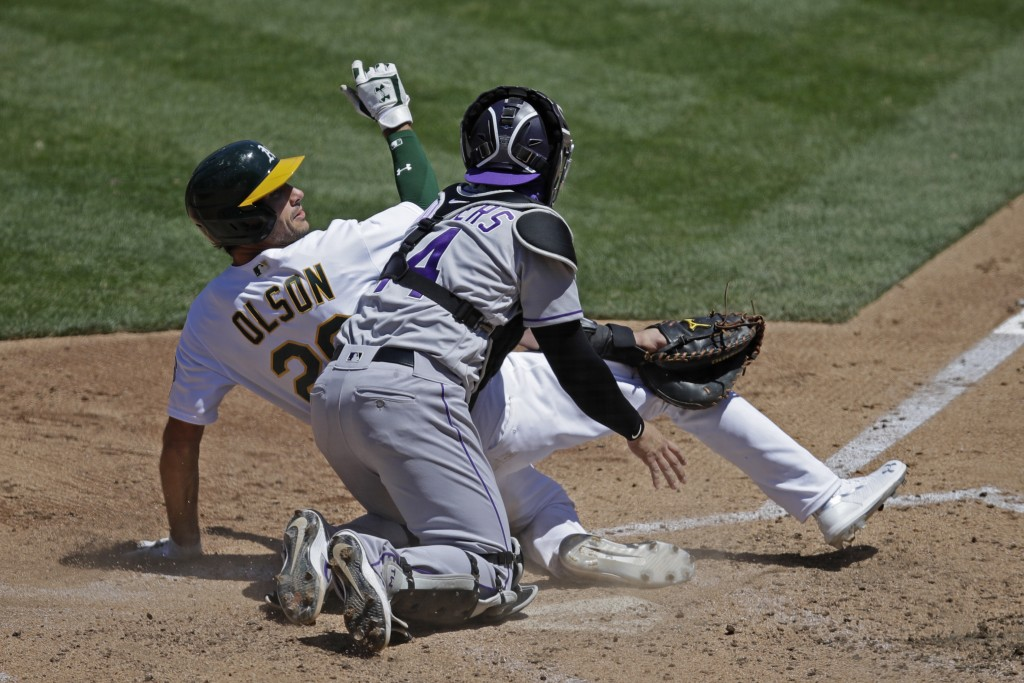 Colorado Rockies catcher Tony Wolters (14) tags out Oakland Athletics' Matt Olson, left, during the fourth inning of a baseball game Wednesday, July 2...