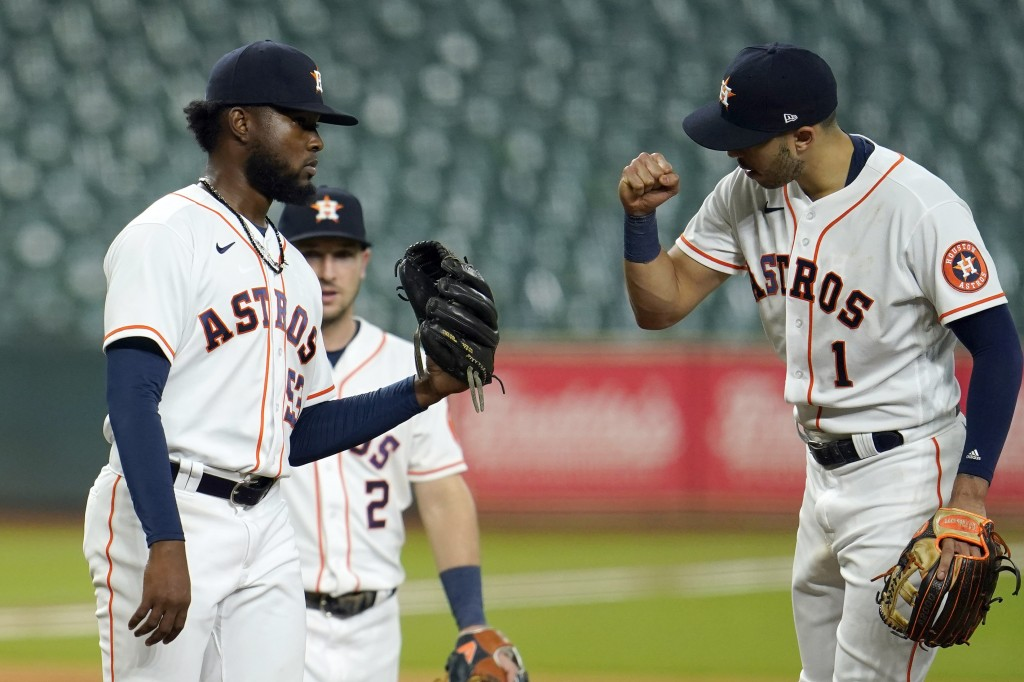 Houston Astros starting pitcher Cristian Javier, left, gets a fist bump from second baseman Carlos Correa (1) as he waits for manager Dusty Baker to p...