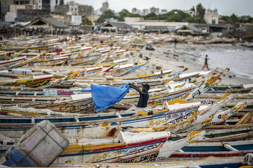 A fisherman dries a sheet next to fishing boats that are grounded because demand for fish dries up during the upcoming Islamic holiday of Eid al-Adha ...