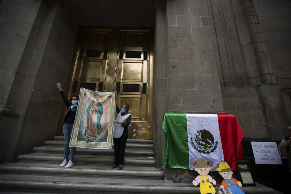 Activists against abortion hold up an image of Our Lady of Guadalupe at the entrance of the Supreme Court to celebrate the court's decision against an...