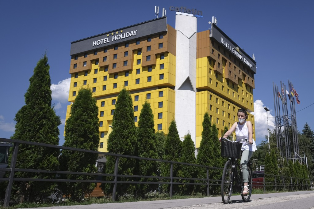 A woman rides a bicycle passing the Holiday Hotel, which opened in 1984 as Holiday Inn, a luxurious accommodation for world's royalty, film stars and ...