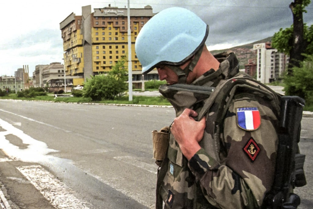 FILE - In this Sunday May 14, 1995 file photo, a French UN peacekeeper stands by his anti-sniper position backdropped by the Holiday Inn hotel on Sara...