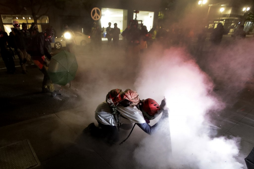 A demonstrator kneels and uses a makeshift shield as federal agents launch tear gas during a Black Lives Matter protest at the Mark O. Hatfield United...