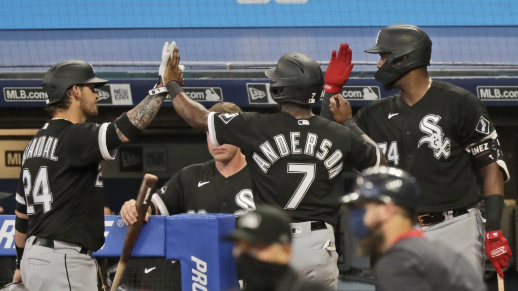 Chicago White Sox's Tim Anderson (7) is congratulated by teammates after scoring in the ninth inning in a baseball game against the Cleveland Indians,...