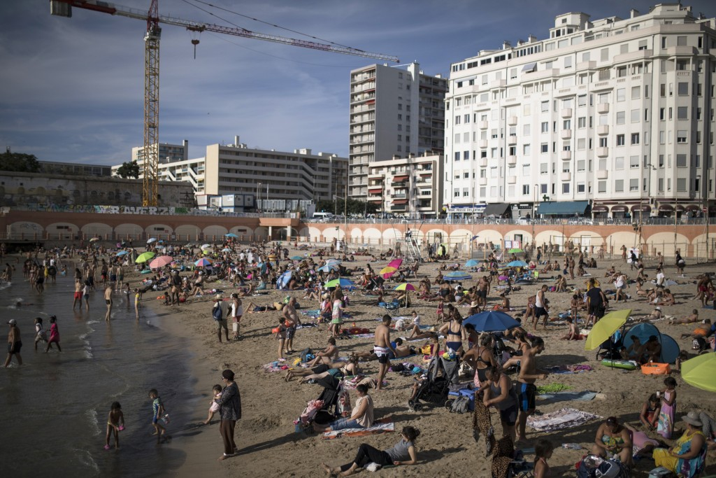 FILE - In this July 25, 2020, file photo, beachgoers enjoy the sun at the Plage des Catalans in Marseille, southern France. An outbreak among 18- to 2...