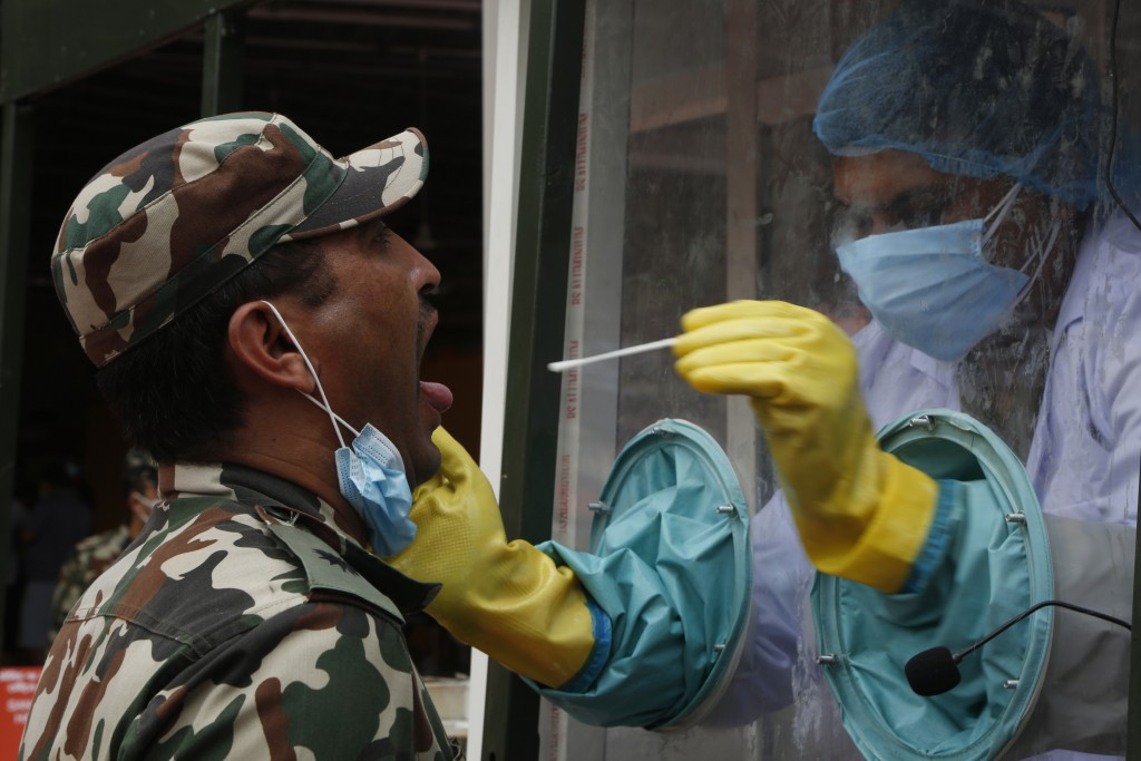 A health worker in a mobile swab collection vehicle collects samples from a Nepalese army man for COVID-19 test in Kathmandu, Nepal, Thursday, July 30...