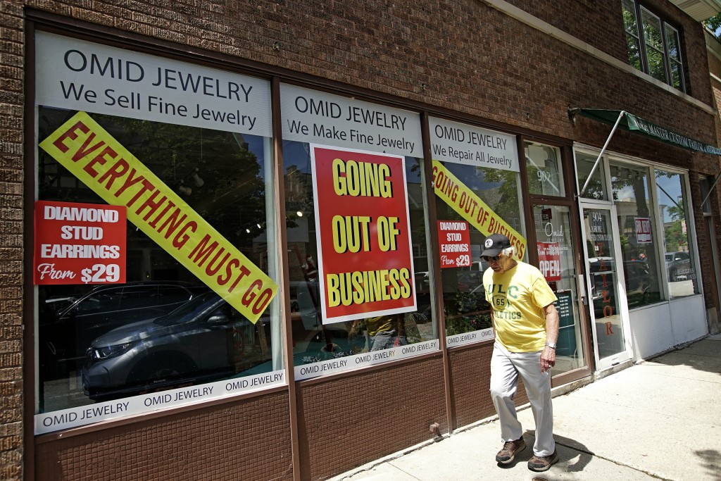 FILE - A man walks past a retail store that is going out of business due to the coronavirus pandemic in Winnetka, Ill., Tuesday, June 23, 2020.  More ...