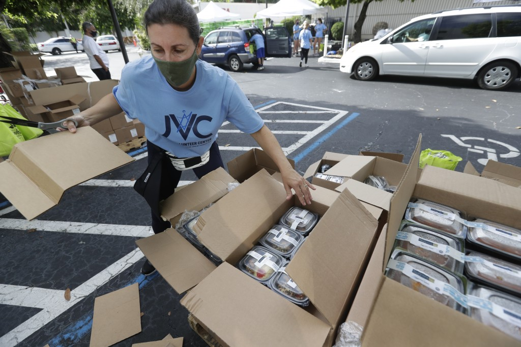 Volunteer Malka Rodrig unpacks meals at a kosher food drive-thru distribution site, Wednesday, July 29, 2020, at the Greater Miami Jewish Federation b...