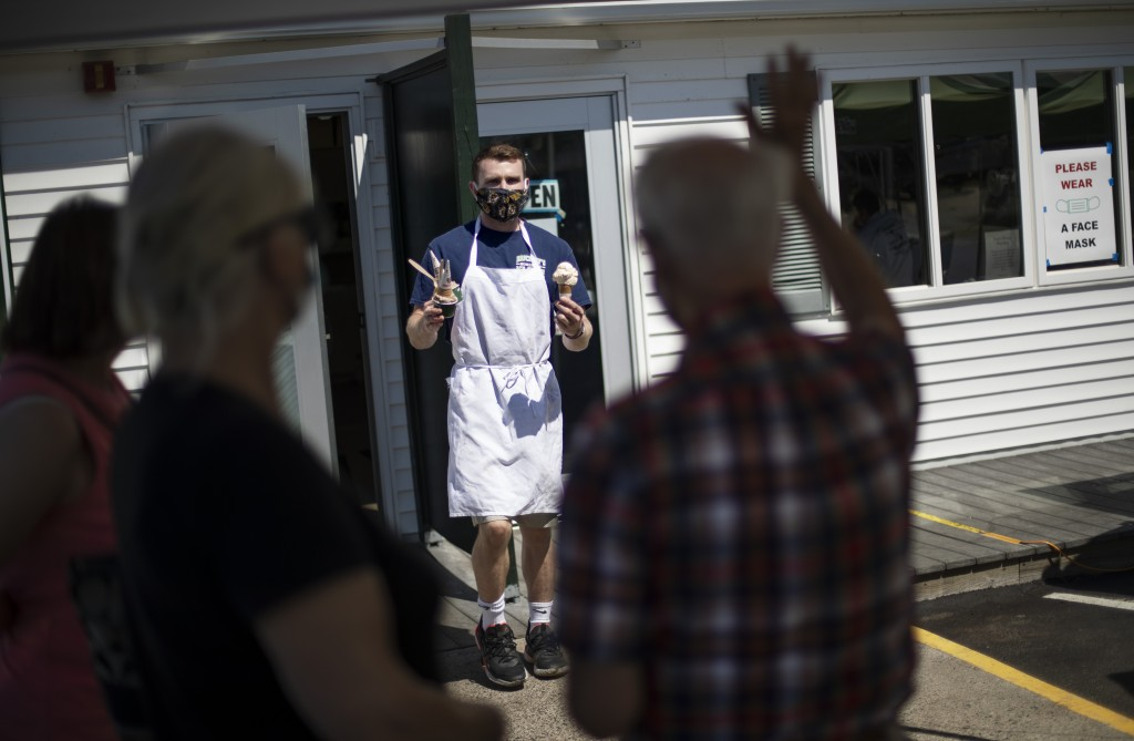 Brendan Kenny serves customers with masks at a Brickley's Ice Cream shop, one of two stores, in Narragansett, R.I., Wednesday, July 29, 2020. The othe...