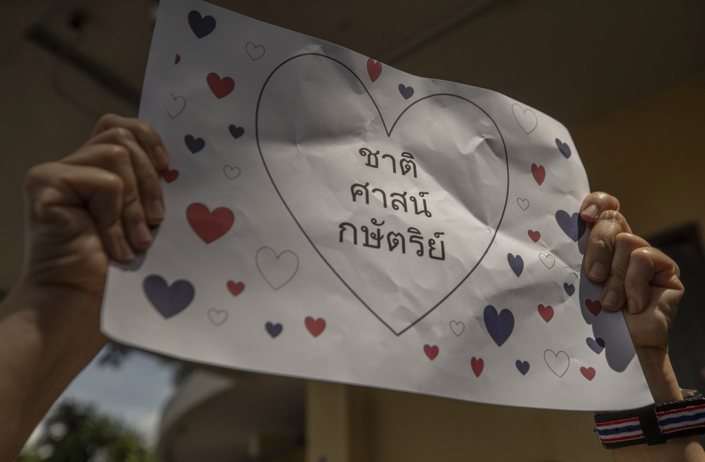 """A supporter of Thailand's monarchy hold a poster that reads """" Nation, Religion, and Monarchy"""", during a gathering to show concerns over the country's ..."""