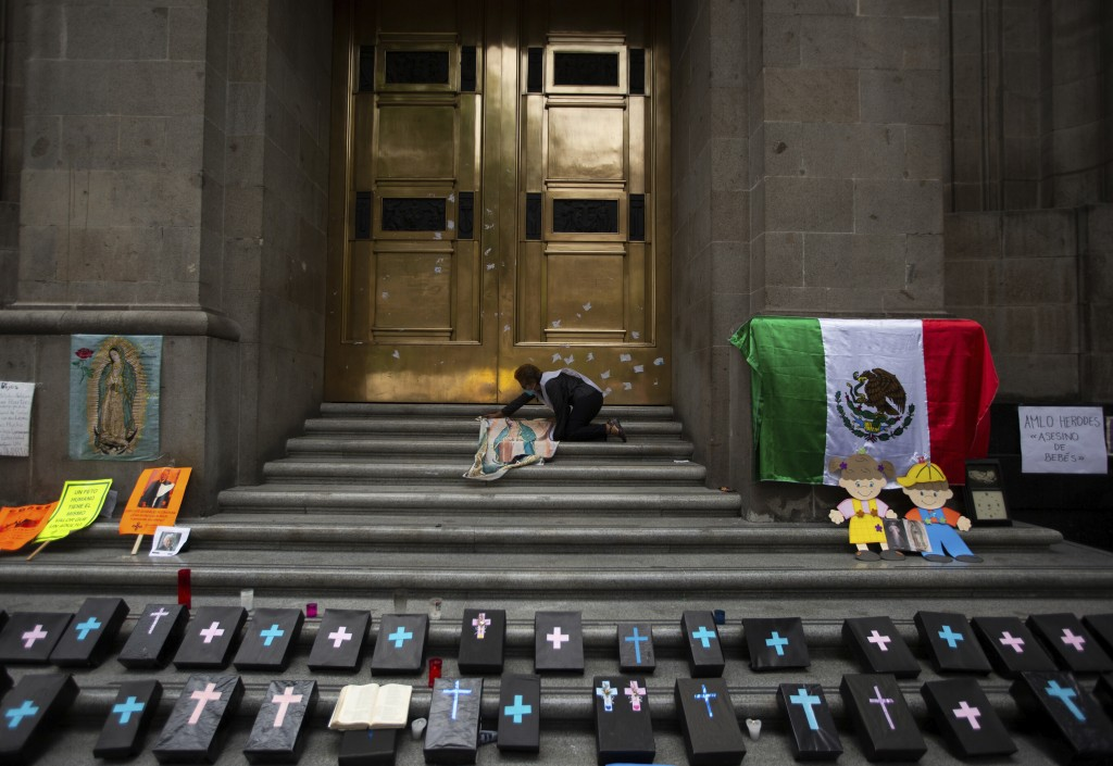 An activist against abortion places an image of Our Lady of Guadalupe alongside small, mock coffins at the entrance to the Supreme Court to celebrate ...