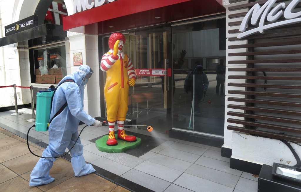 An employee disinfects a closed mall in Mumbai, Thursday, July 30, 2020. Malls and market complexes will reopen on Aug. 5. However theaters, food cour...