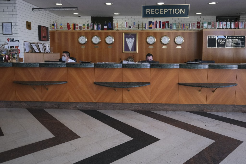 Staff, wearing face masks against the COVID-19 infection, sit at the reception desk of the Holiday Hotel in Sarajevo,  Wednesday, July 29, 2020, which...