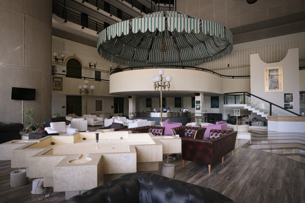 Staff members work at the bar of the Holiday Hotel, which opened as Holiday Inn, a luxurious accommodation for world's royalty, film stars and other d...