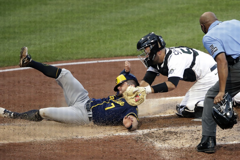 Pittsburgh Pirates catcher Jacob Stallings, center, tags out Milwaukee Brewers' Eric Sogard (7) with umpire C.B. Bucknor making the call during the th...