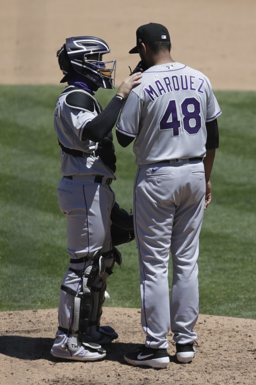 Colorado Rockies' Tony Wolters, left, speaks with pitcher German Marquez (48) during the fifth inning of a baseball game against the Oakland Athletics...