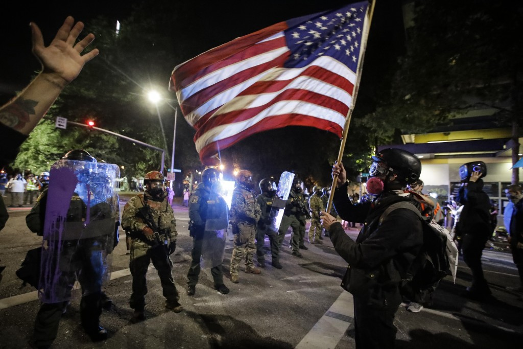 A demonstrator waves a U.S. flag in front of federal officers after tear gas is deployed during a Black Lives Matter protest at the Mark O. Hatfield U...