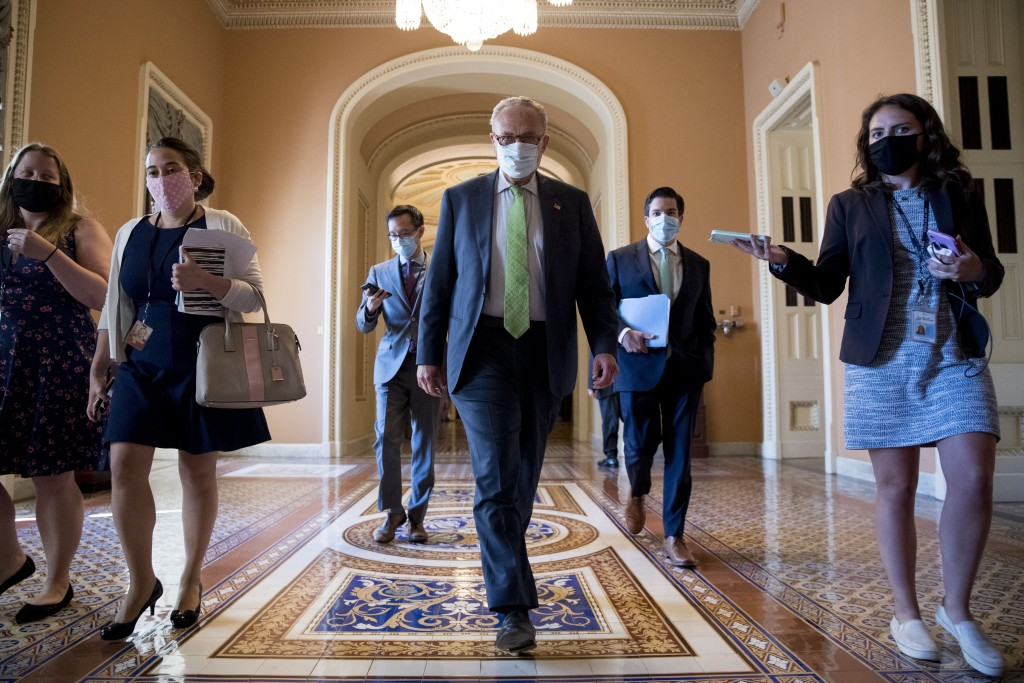 Senate Minority Leader Sen. Chuck Schumer of N.Y. walks to the office of House Speaker Nancy Pelosi of Calif., on Capitol Hill in Washington, Wednesda...