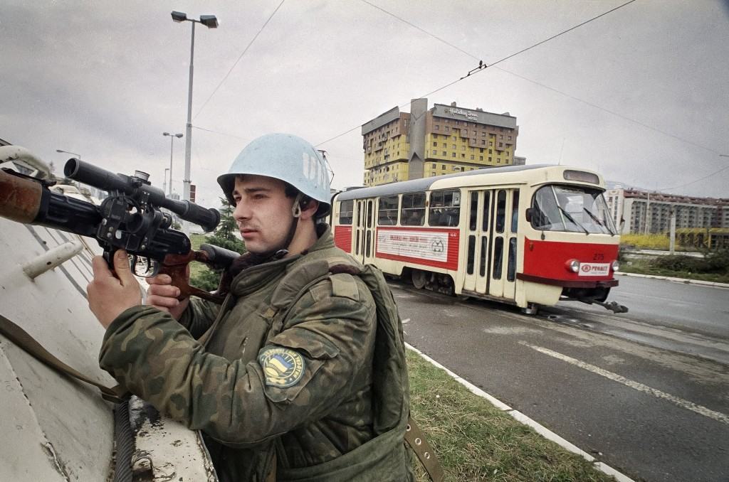 FILE - In this Sunday, March 27, 1994, file photo, a Ukrainian U.N. soldier holds a weapon while protecting a tram diving through the so called Sniper...