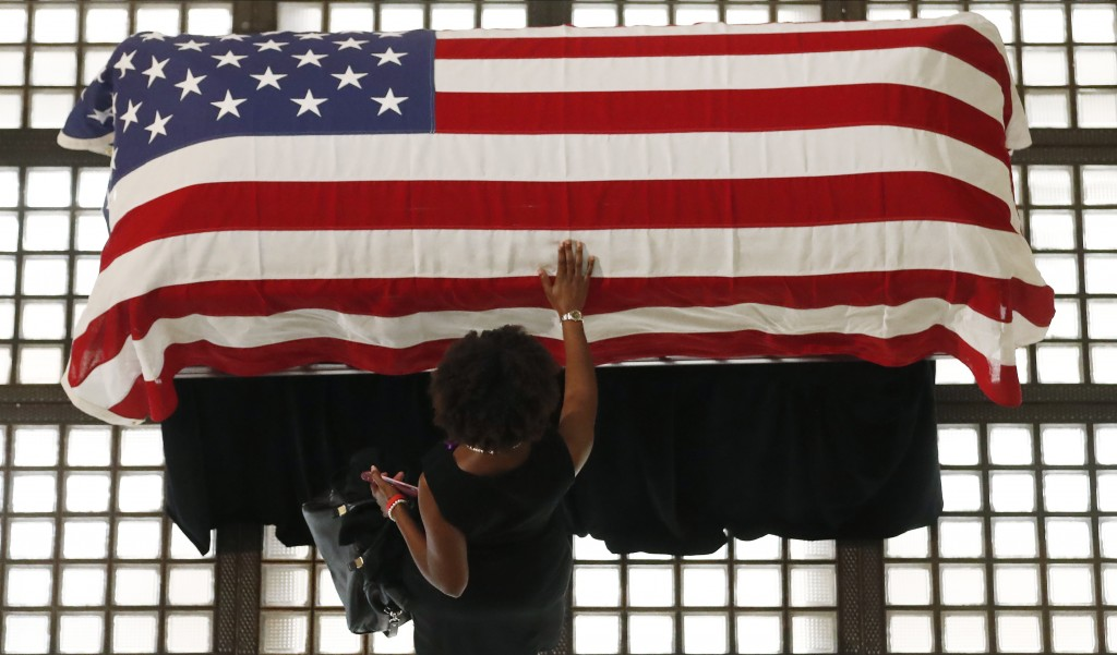 A mourner pauses by the casket of Rep. John Lewis lying in repose at the state capital, Wednesday, July 29, 2020, in Atlanta. Lewis, who carried the s...