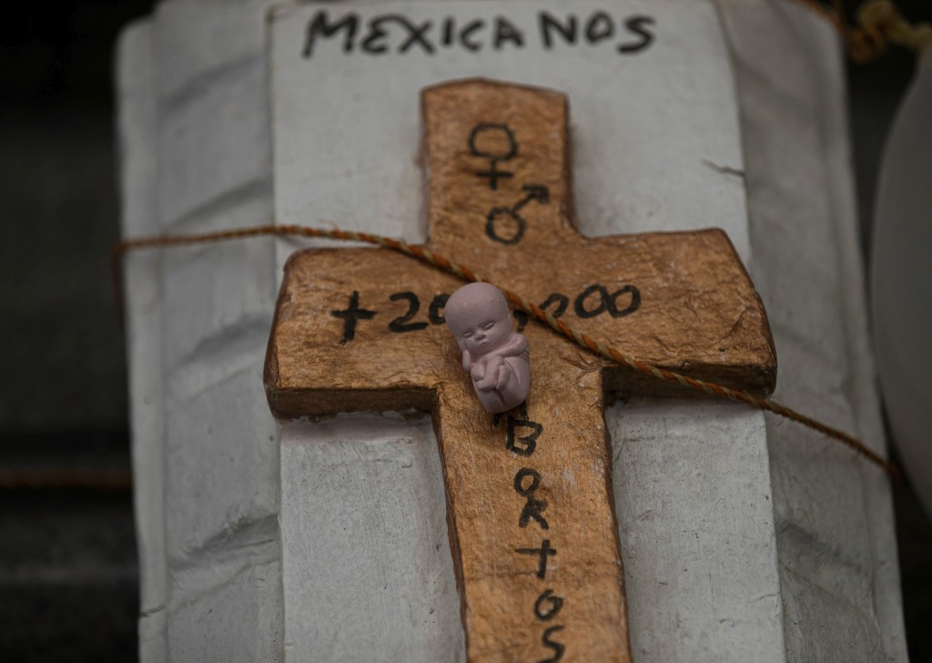 A mock coffin featuring a cross and tiny statue fo a fetus lays outside the Supreme Court that ruled against an injunction in Veracruz state aiming to...