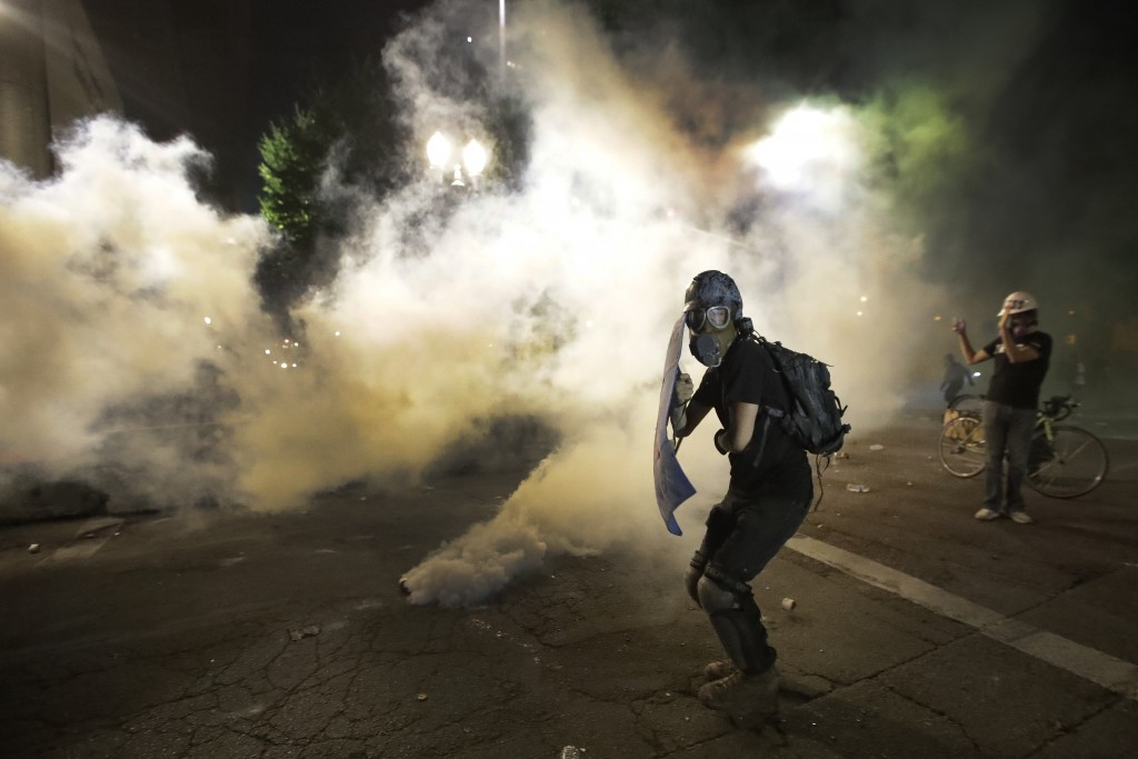 A demonstrator tries to shield himself from tear gas deployed by federal agents during a Black Lives Matter protest at the Mark O. Hatfield United Sta...