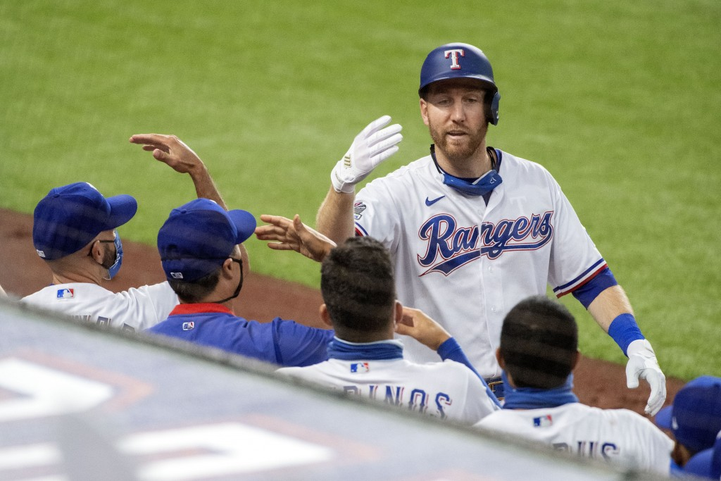 Texas Rangers' Todd Frazier celebrates with teammates after his solo home run off of Arizona Diamondbacks starting pitcher Madison Bumgarner during th...