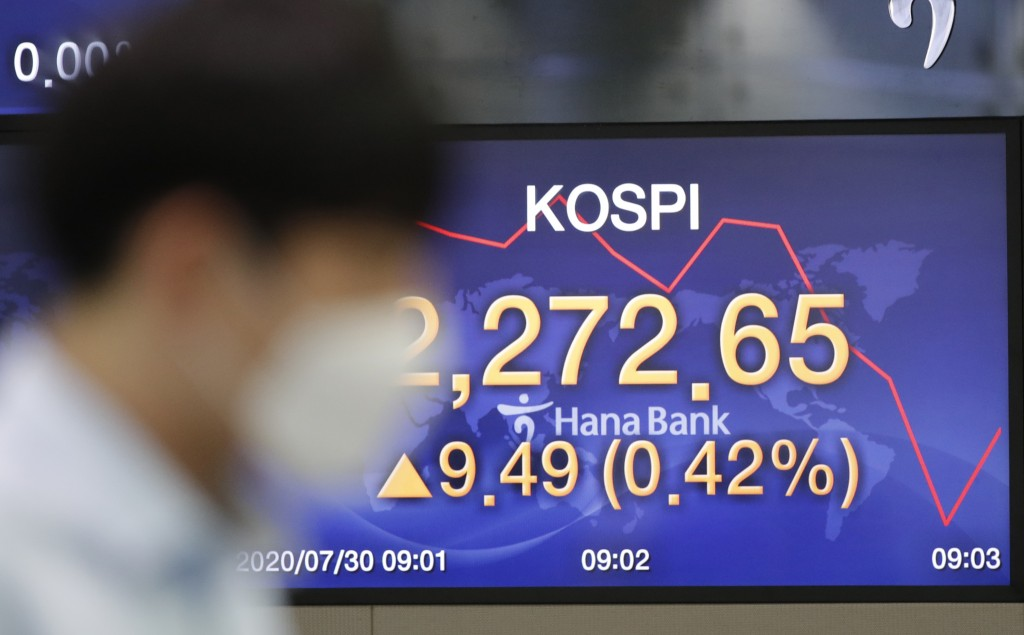 A currency trader walks near the screen showing the Korea Composite Stock Price Index (KOSPI) at the foreign exchange dealing room in Seoul, South Kor...