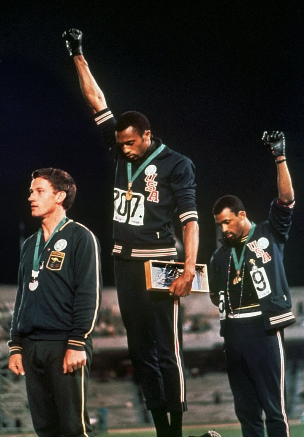 FILE - In this Oct. 16, 1968, file photo, extending gloved hands skyward in racial protest, U.S. athletes Tommie Smith, center, and John Carlos stare ...