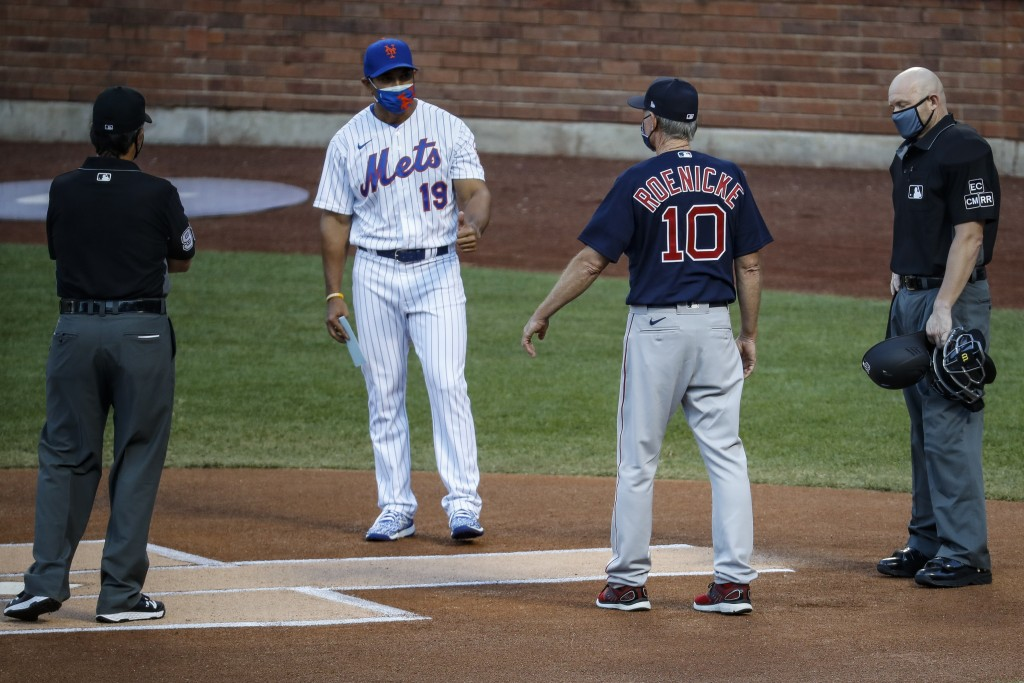 New York Mets manager Luis Rojas (19) and Boston Red Sox manager Ron Roenicke (10) maintain social distance during a meeting at home plate before a ba...